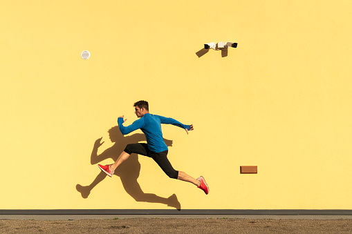 Sportive man exercising at yellow wall with CCTV camera - gettyimageskorea