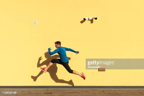 sportive man exercising at yellow wall with cctv camera - rennen stockfoto's en -beelden