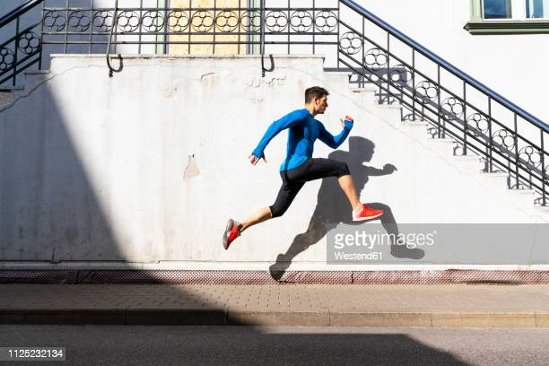 sportive man exercising on pavement - center athlete stock pictures, royalty-free photos & images