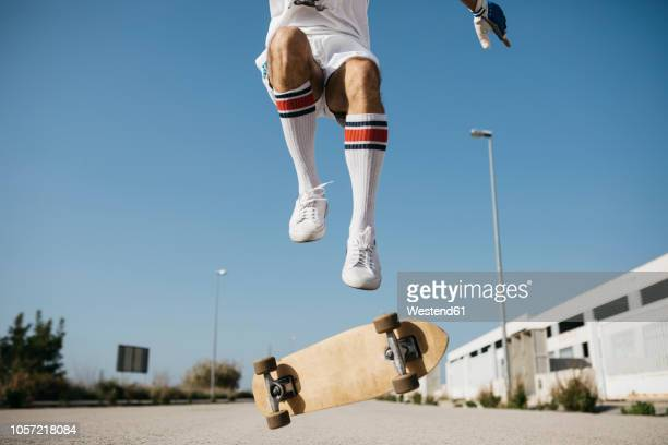 sportive man jumping above ground with skateboard performing trick - white shoe stock pictures, royalty-free photos & images