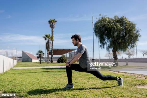 sportive man stretching on a meadow - precalentamiento fotografías e imágenes de stock