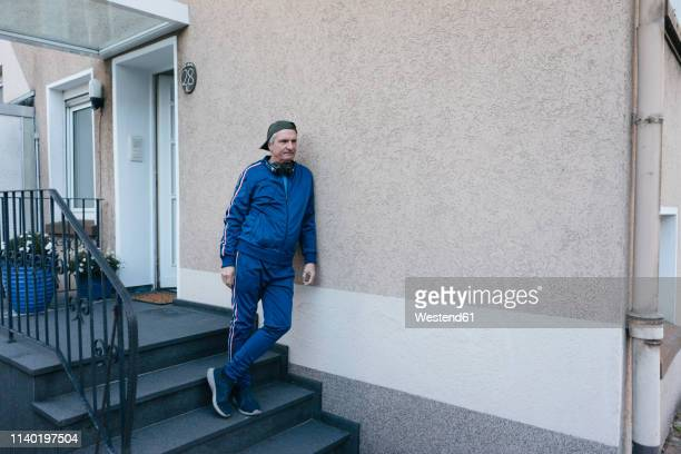 sportive senior man in tracksuit leaning against house wall - trainingsanzug stock-fotos und bilder