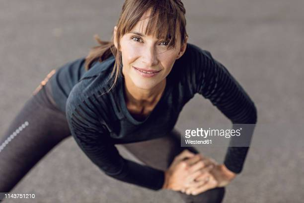 sportive woman doing her fitness training outdoors, stretching - sport stock-fotos und bilder