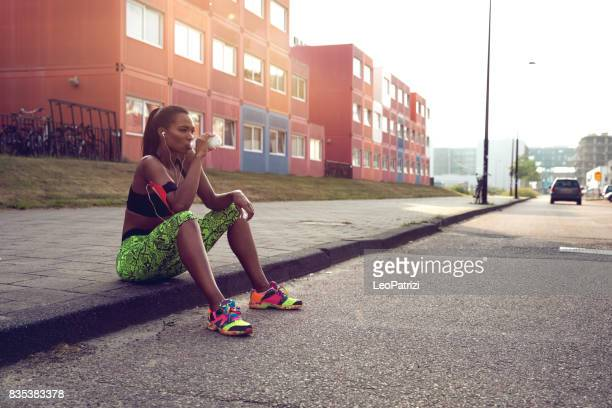 sportive woman getting fit in an urban industrial area - energy drink stock pictures, royalty-free photos & images