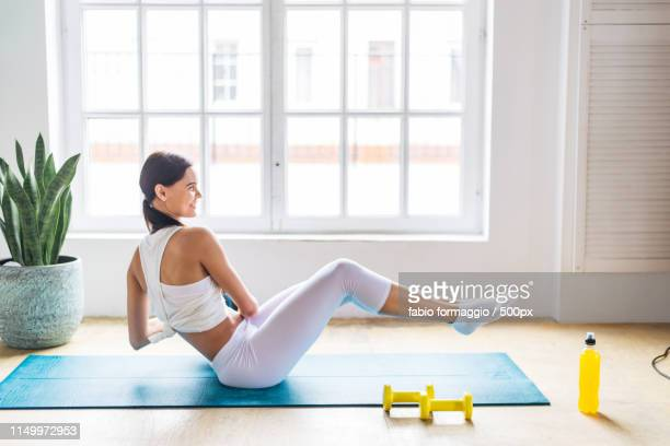 sportive woman training at home - core stock pictures, royalty-free photos & images