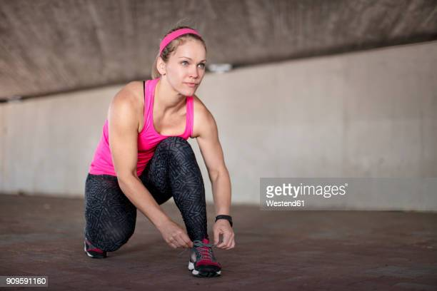 sportive woman tying her shoes - pink shoe stock pictures, royalty-free photos & images