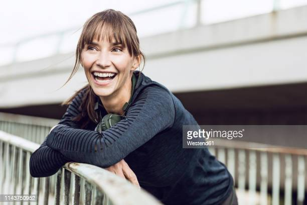 sportive woman with headphones, doing her fitness training outdoors - athleticism stock pictures, royalty-free photos & images