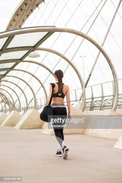 sportive woman with sports bag walking, rear view - sportswear stock pictures, royalty-free photos & images