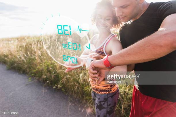 sportive young couple having a break checking data emerging from smartwatch - wearable computer stock pictures, royalty-free photos & images