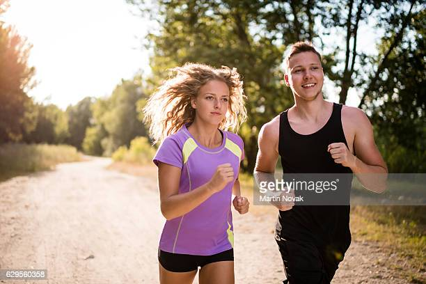 Sportive young couple jogging outdoors