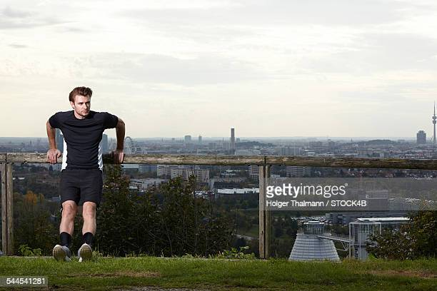 Sportive young man stretching with skyline of Munich in background, Bavaria, Germany
