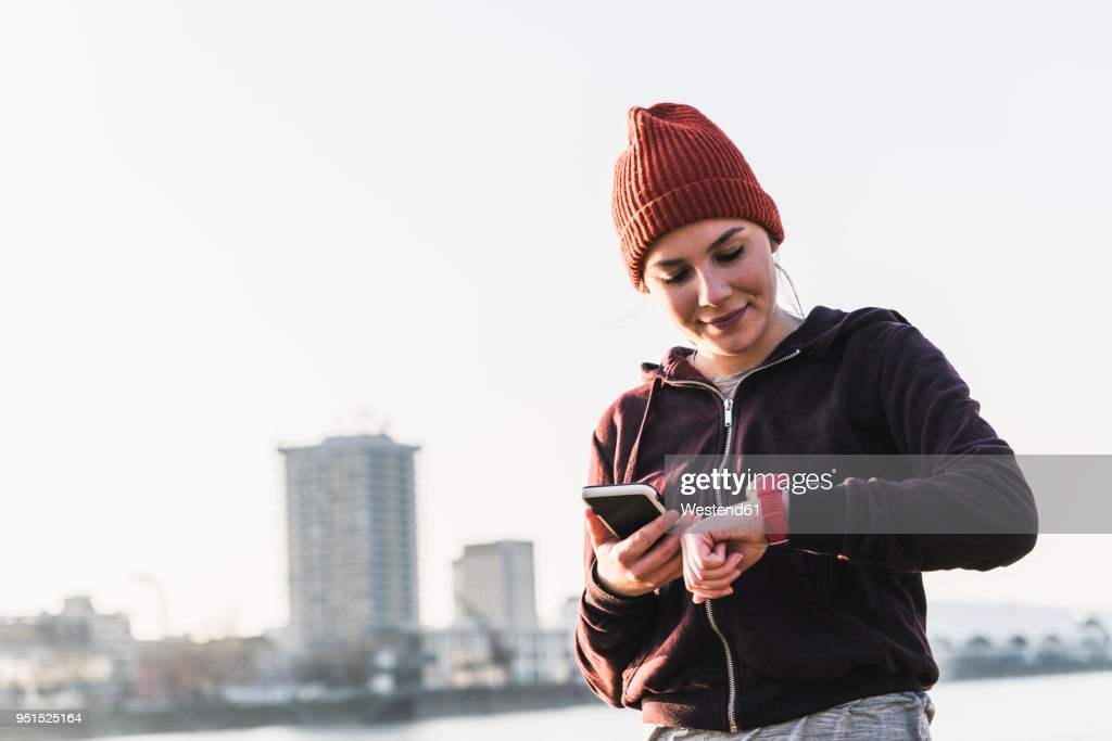 Sportive young woman at the riverside in the city with smartphone and smartwatch : Stock Photo