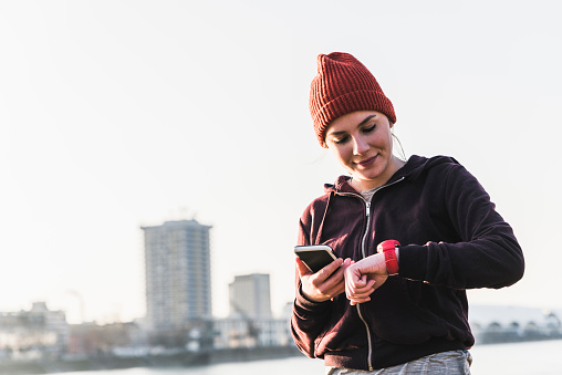 Sportive young woman at the riverside in the city with smartphone and smartwatch - gettyimageskorea