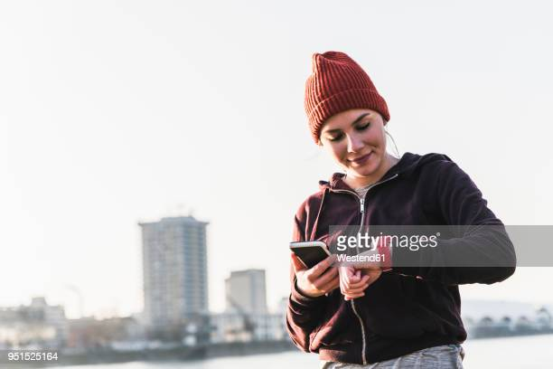 sportive young woman at the riverside in the city with smartphone and smartwatch - sport stock-fotos und bilder