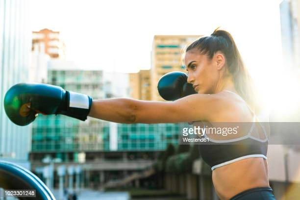 sportive young woman boxing in the city - 戦う ストックフォトと画像