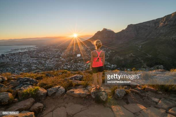 Sportive young woman contemplating sunrise from mountain top
