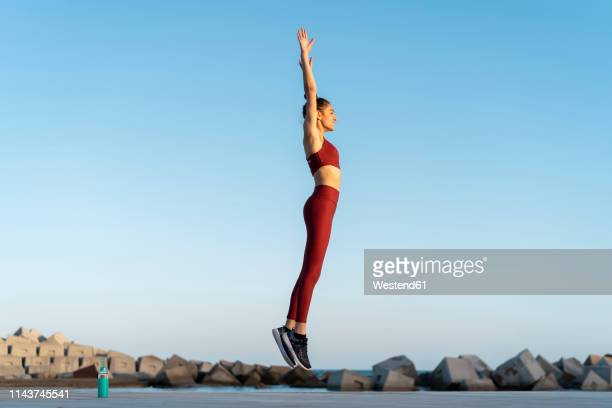 sportive young woman during workout, jumping - red trousers stock pictures, royalty-free photos & images