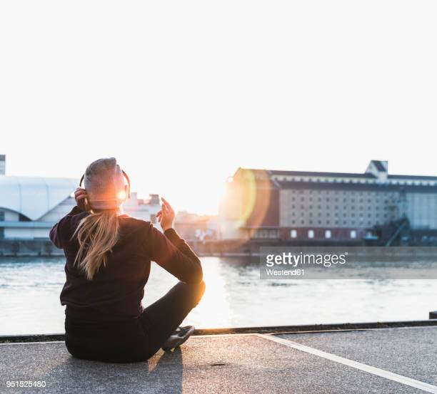 sportive young woman having a break at the riverside in the city at sunset - sportlichkeit stock-fotos und bilder
