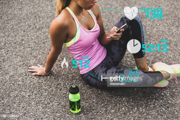 sportive young woman having a break with data emerging from smartphone - caucasian appearance stock pictures, royalty-free photos & images