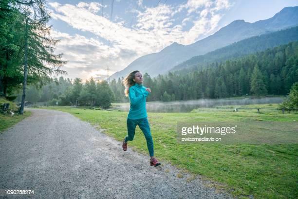 Sportlich junge Frau joggt im Freien, Trail Lauferlebnis. Menschen körperbewusstes und heulendes Lifestyle-Konzept.