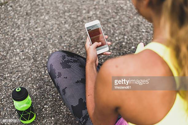 Sportive young woman looking at graph on cell phone display