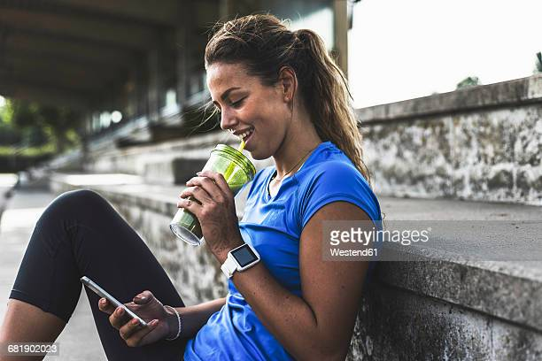 Sportive young woman sitting on grandstand with cell phone and drinking mug