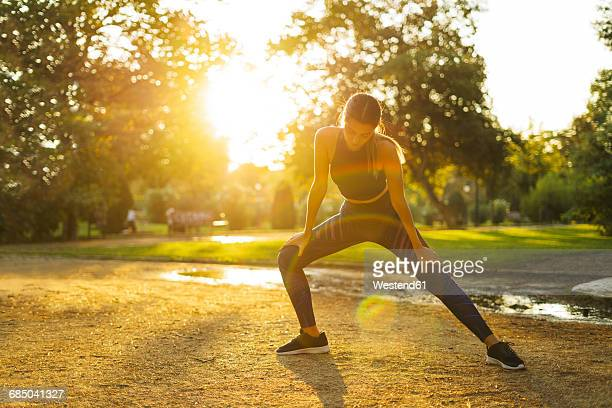 Sportive young woman stretching in park at sunset