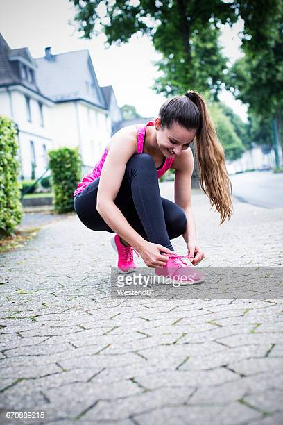 Sportive young woman tying her shoes