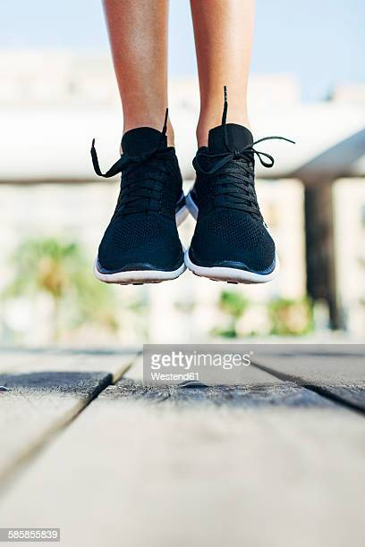 Sportive young woman wearing black sneakers jumping in the air, close-up