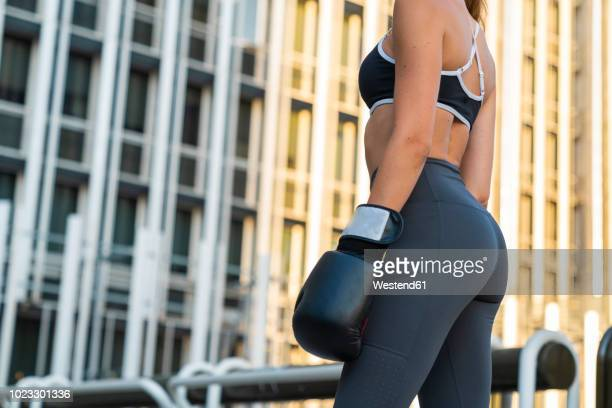 sportive young woman with boxing gloves in the city in front of a high-rise building - culos fotografías e imágenes de stock