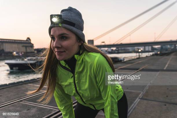 sportive young woman with headlamp at dusk at the riverside in the city - sportlichkeit stock-fotos und bilder