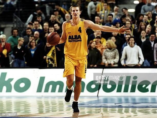 Sportler Basketball D dribbelt mit dem Ball und zeigt mit denFingern den Spielzug an