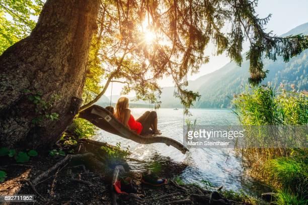 Sportliche Frauen relaxen am Seeufer auf einer Hängeschaukel