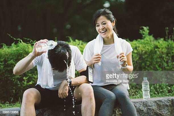 sportman pouring water on his head after workout - women in wet t shirts stock photos and pictures