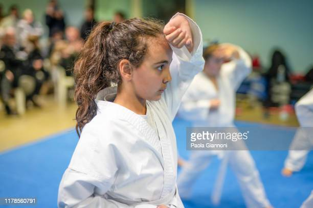 sports and disciplines. martial arts. pre-teen girl during a karate class in gym - judo stock pictures, royalty-free photos & images