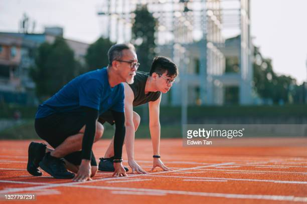 sports asian chinese senior athletes father and son lining up getting ready starting line running at track and run towards finishing line in the morning at track and field stadium - forward athlete stock pictures, royalty-free photos & images