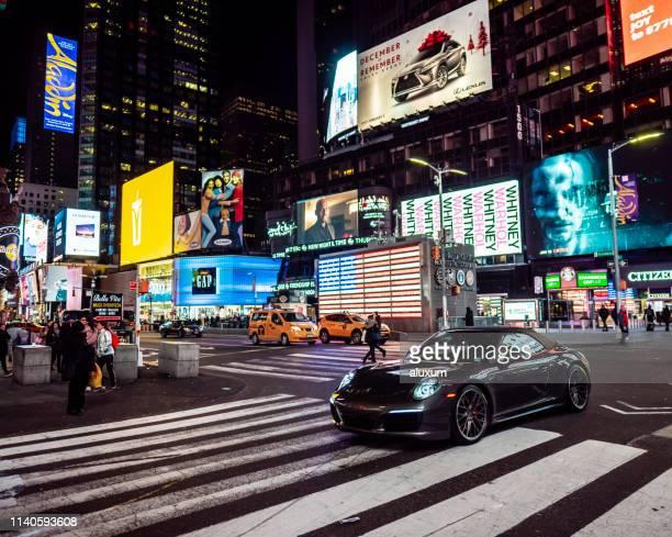 sportwagen fahren nachts am times square new york city - porsche stock-fotos und bilder