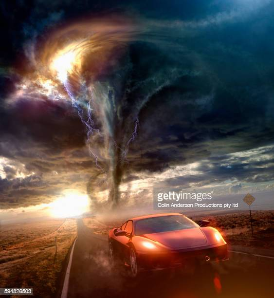 Sports car driving away from tornado