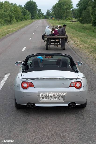 A sports car driving behind a horse cart on a road