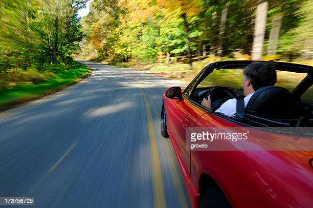 Sports car driving on a country road.