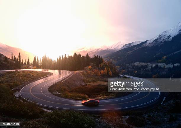 sports car driving on winding remote road - road stock pictures, royalty-free photos & images