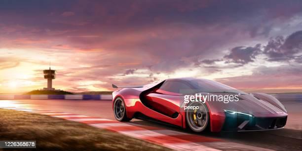 voiture de sport se déplaçant à grande vitesse sur l'hippodrome au coucher du soleil - circuit automobile photos et images de collection