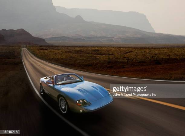sports car on remote highway - sports car stock pictures, royalty-free photos & images