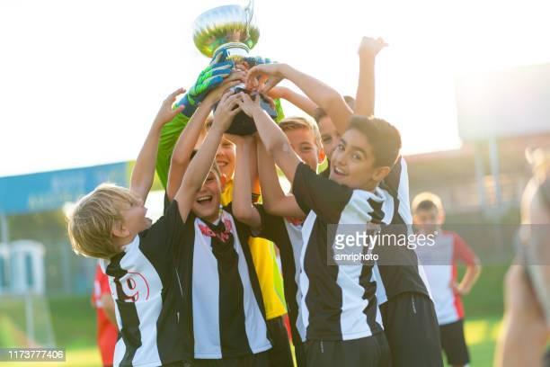 campeones de deportes felices niños jugadores de fútbol celebrando la copa - podio del ganador fotografías e imágenes de stock