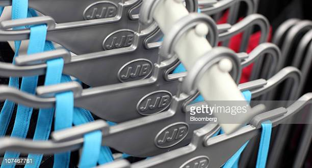 Sports clothing is displayed on hangers at a JJB store operated by JJB Sports Plc in Slough UK on Thursday Dec 9 2010 While snow and freezing...