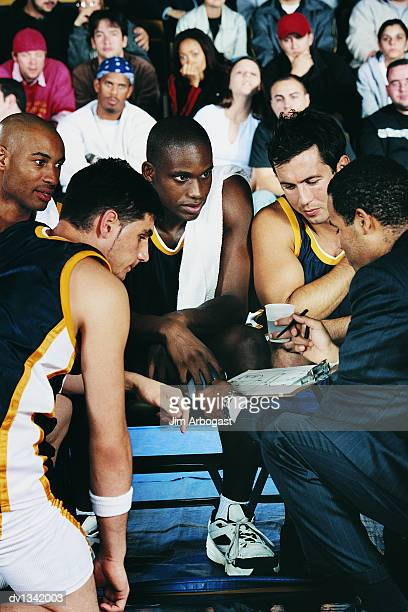 Sports Coach Giving His Basketball Players a Pep Talk in a Basketball Court in Front of the Audience in the Stands