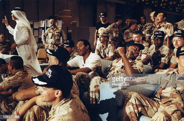 NBC Sports commentator and former professional football player OJ Simpson center watches a Thanksgiving Day football game with United States troops...