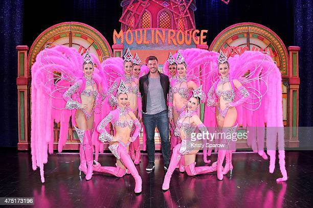 Sports Commentator Jesse Palmer poses backstage with dancers at Le Moulin Rouge on May 29 2015 in Paris France