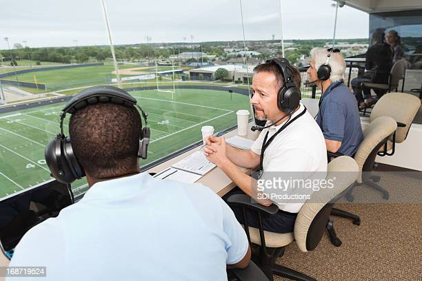 sports commentators discussing football game in the press box - commentator stock pictures, royalty-free photos & images