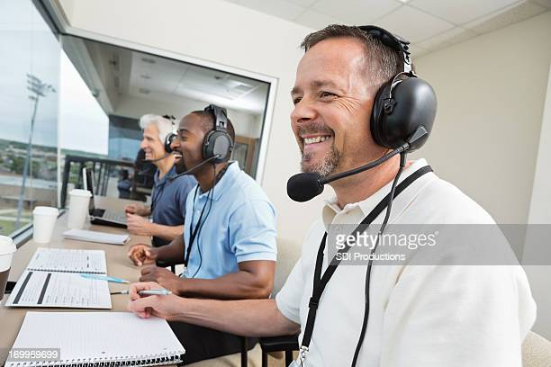 sports commentators wearing headsets; reporting from stadium press box - commentator stock pictures, royalty-free photos & images